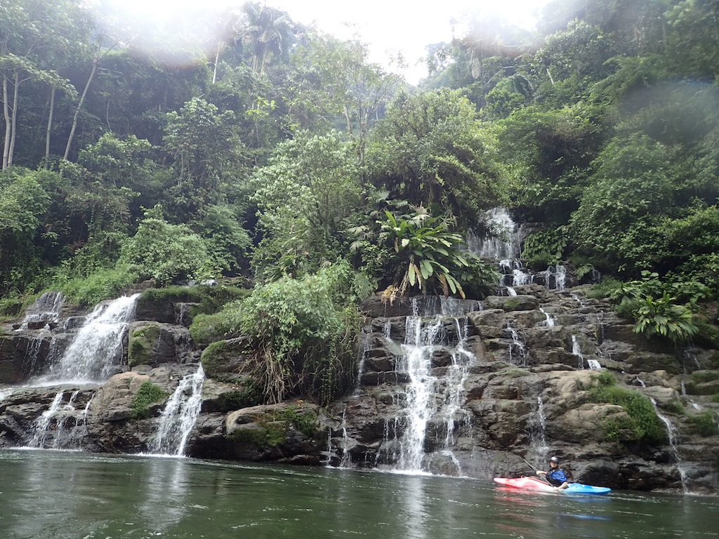 A kayaker pauses by an incredible waterfall in Ecuador