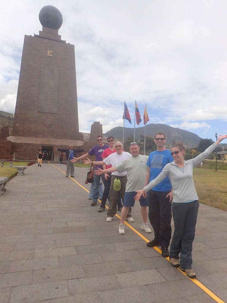 A rafting group posing by an important building in Ecuador