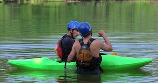 An adult kayaking student listens to an instructor during a private session