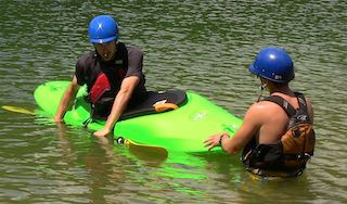 A student preps for a new move during a private kayaking instruction session
